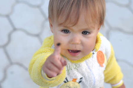 mote: Little girl looking up on the spot on finger
