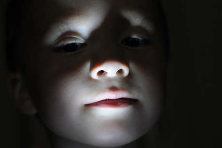 blackness: Little boy portrait in the dark lighted from the bottom
