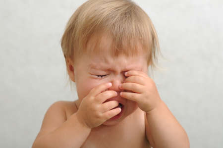 Screaming crying caucasian baby rubbing her eyes