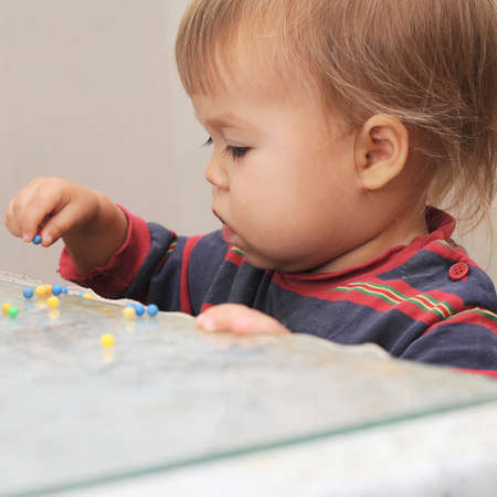 Little baby playing with colored pills on the table Stock Photo