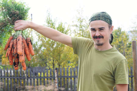 Happy agronome with bunch of fresh carrots Stock Photo