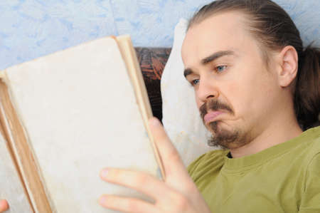 bewildered: bewildered young caucasian man reading vintage book Stock Photo