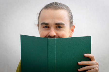 bookish: Young man smiling peeping from behind the book