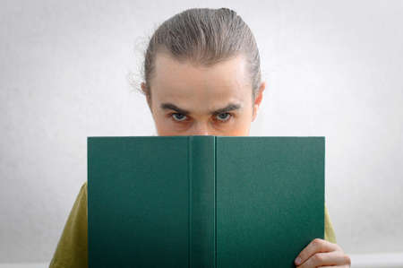 bookish: Young man looking from behind the book