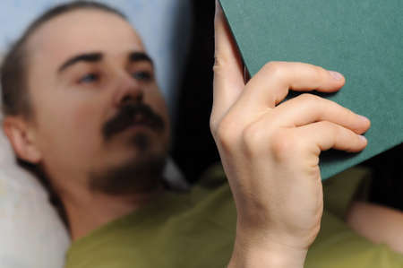 bookish: man reading literary book lying on coach