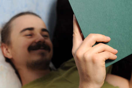 bookish: Happy man reading literary book lying on coach