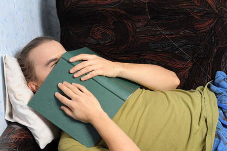 bookish: man student tired of reading book lying on coach Stock Photo