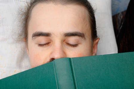bookish: man student tired of reading book and sleeping