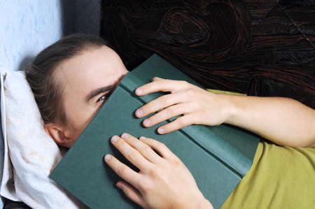 bookish: Young man peeping from behind the book