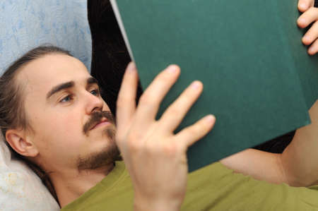 bookish: Man with mustache reading book lying on sofa Stock Photo