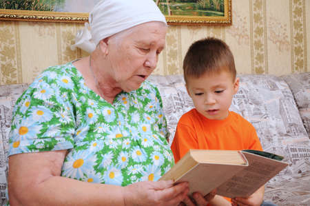 descendant: Grandmother reading book for grandson in a home environment Stock Photo