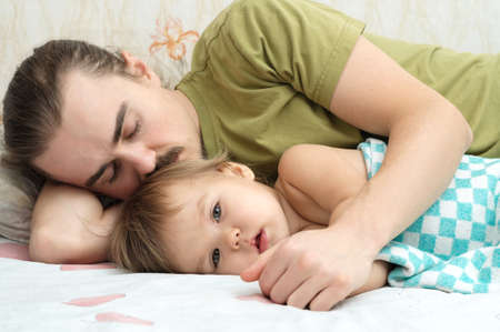 dad and child: Cute baby ailing and lying with daddy sad