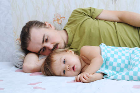 ailing: Cute baby ailing and lying with daddy sad