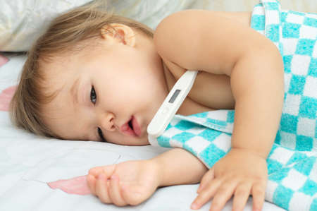 fever: Baby ailing and lying measuring electric thermometer Stock Photo