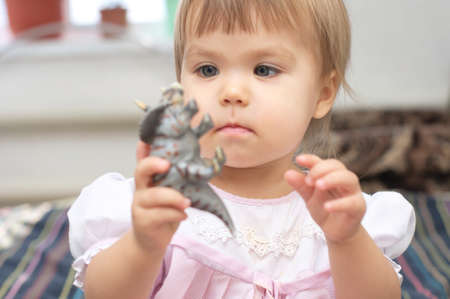 triceratops: Little girl playing with dinosaur Triceratops toy