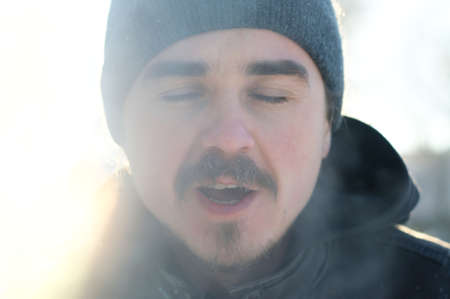 exhale: Siberian man with beard portrait in warm winter clothes exhale steam