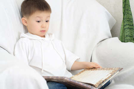 erudition: Boy reading book and amazing of something from the book Stock Photo