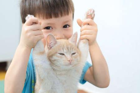 foreleg: Caucasian boy holding front legs of lazy ginger cat Stock Photo