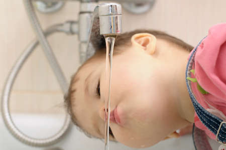 gasping: Thirsty little girl quench her thirst and drinking water from tap Stock Photo