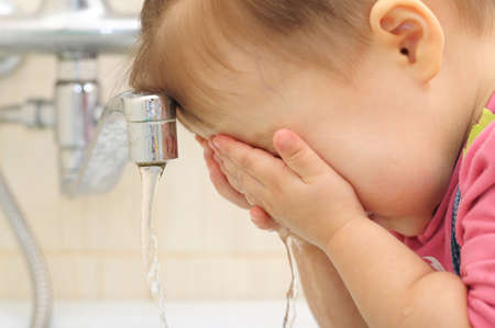 children hands: Little baby washing her face in the bathroom Stock Photo