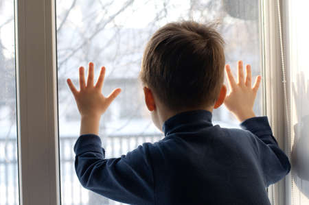 coldness: Boy  looking out the window with hands on the glass