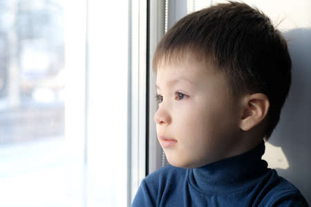philosophical: Boy looking through out the window and thinking smiley philosophical Stock Photo