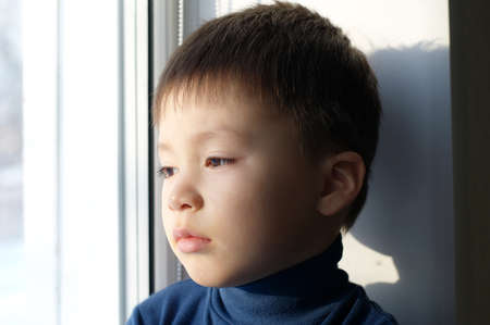 philosophical: Boy portrait sitting on the window and thinking philosophical