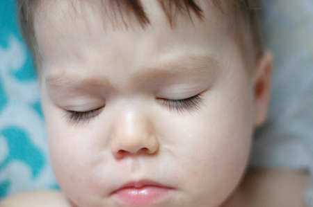 downcast: Baby with long eyelashes  wake up portrait with closed eyes