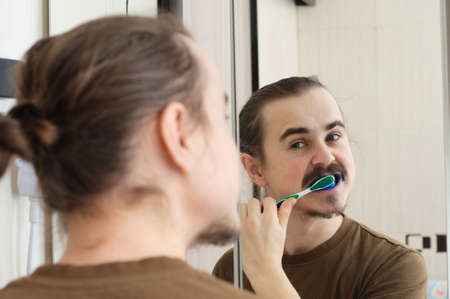 bad color: April joke, coloured tooth brush of young man Stock Photo
