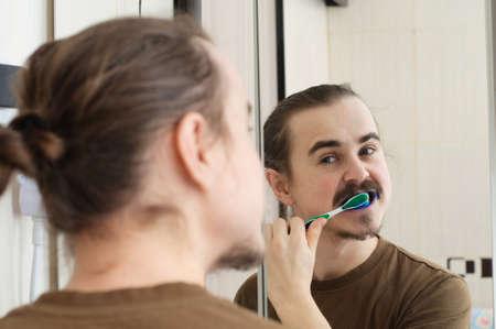 joke: April joke, coloured tooth brush of young man Stock Photo