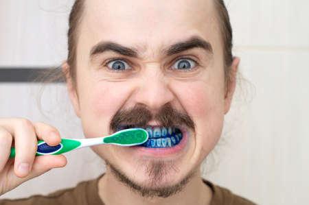 El hombre sobre el cual jugar broma coloreando su cepillo de dientes Foto de archivo