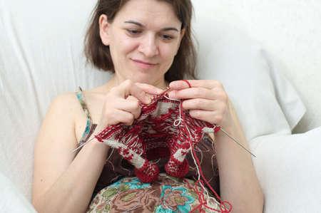 avocation: Sitting smiling caucasian woman  knitting needle yarn Stock Photo