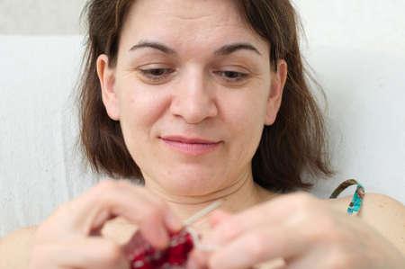 avocation: smiling caucasian woman enjoying with needle knitting
