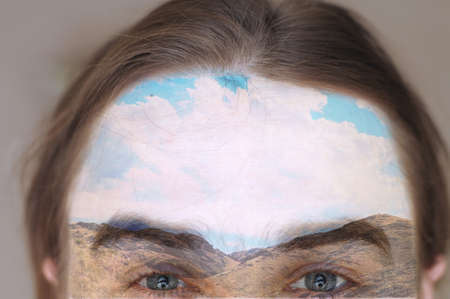 double exposion image of man forehead and sky with mountains