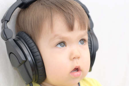 attentively: little girl with headphones listening music attentively