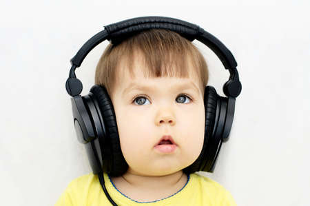 attention: Caucasian little girl attentively listening educational audio program with headphones Stock Photo