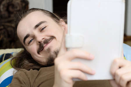 prose: Smiling caucasian moustached man reading tablet in white cover