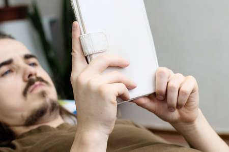prose: Lying caucasian bearded man reading ebook in white cover Stock Photo