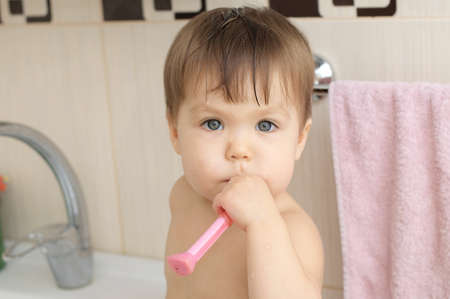 carious: Caucasian little girl cleaning teeth in bathroom