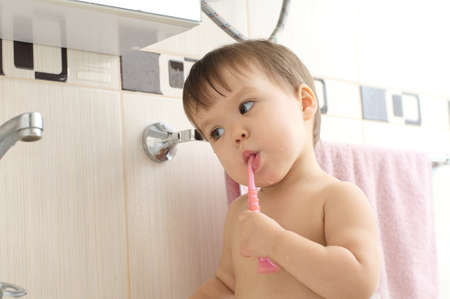 carious: Caucasian baby child brushing teeth in bathroom Stock Photo