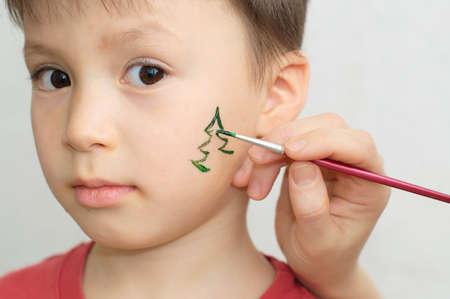 Blanke jongen kind schminken voor kerstfeest