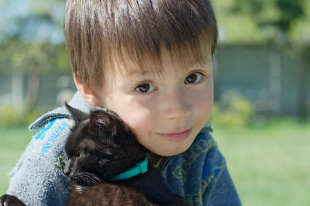 frienship: Boy with black kitten hugging with love