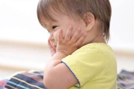 joyfull: Baby caucasian girl holding her sweet cheeks Stock Photo