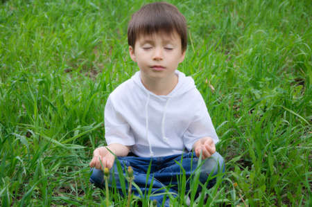 unworried: Caucasian cute boy sitting in meditation pose outside on the grass
