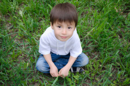 unworried: Caucasian cute boy sitting on the grass and looking up Stock Photo