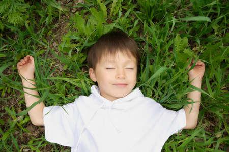 pleasantness: Boy enjoys lying down on the grass