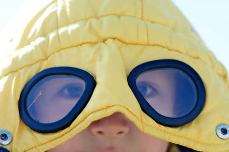 cowl: Boy in yellow coat with glasses outdoor closeup