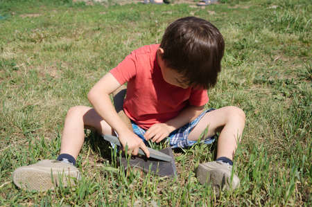 cusp: Caucasian toddler boy scout sharpening axe outdoor