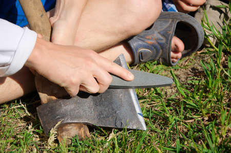 Man hands sharpening ax blade Stock Photo