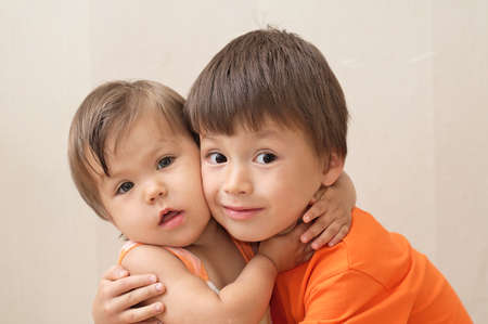 jointly: Older brother and younger sister hugging portrait, Caucasian boy and girl